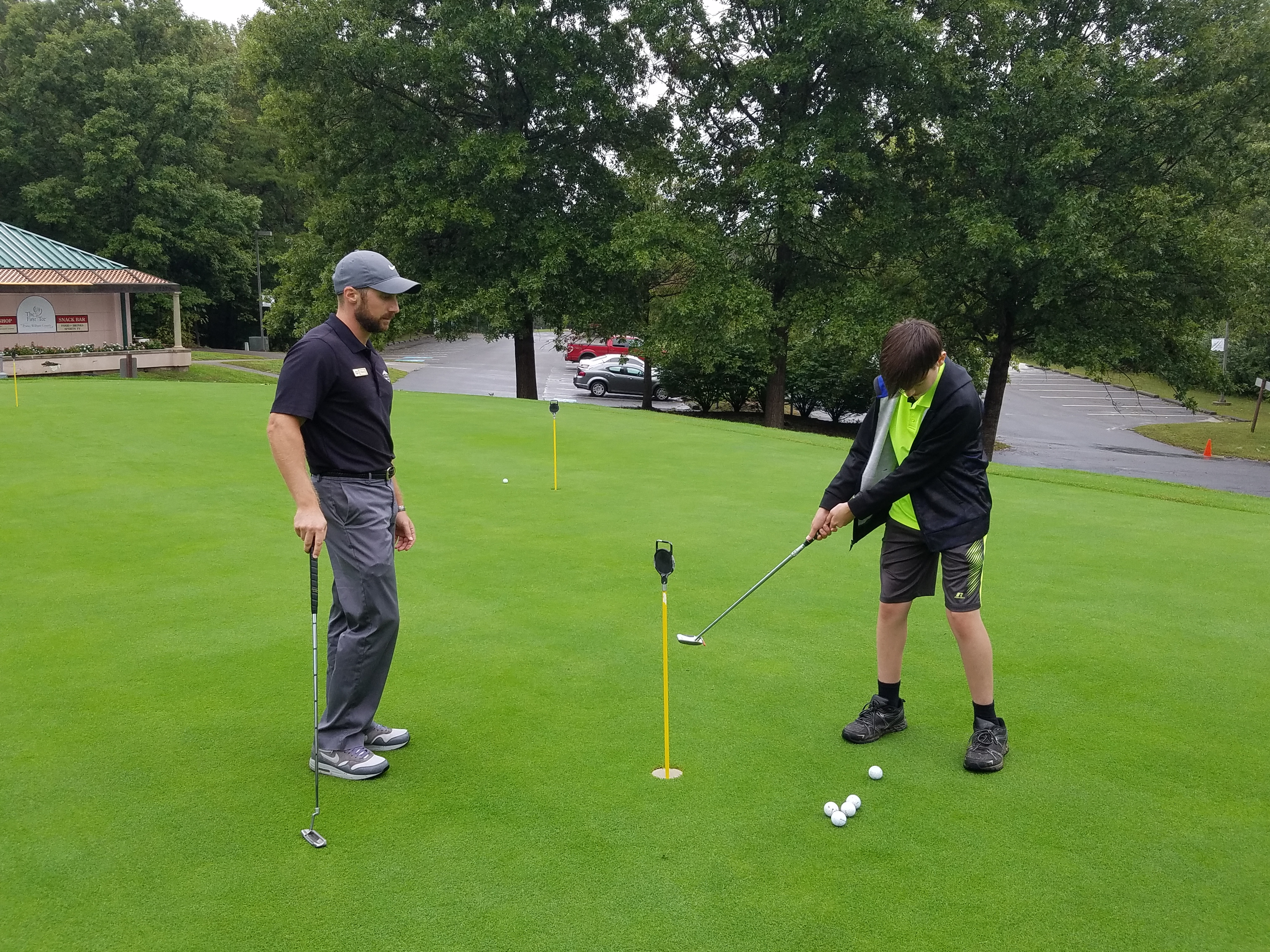 Our Head Golf Pro giving putting lessons to junior golfer at Lake Ridge Golf Course