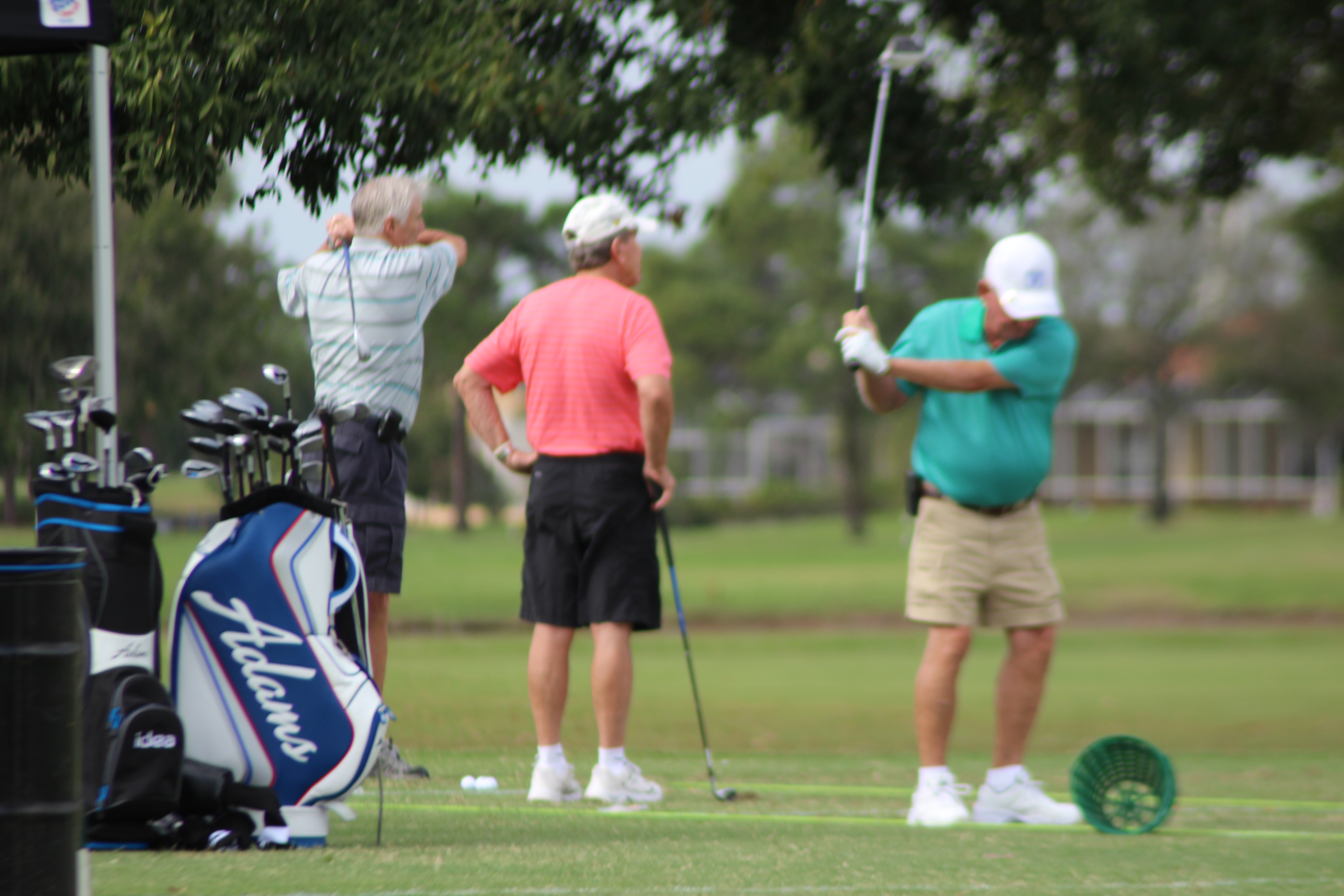 3 guys on the range hitting golf balls, practice your golf game