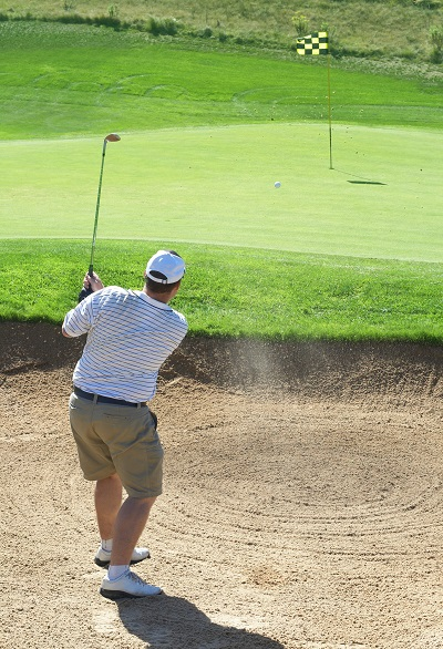 Man Hitting Golf Ball out of Bunker