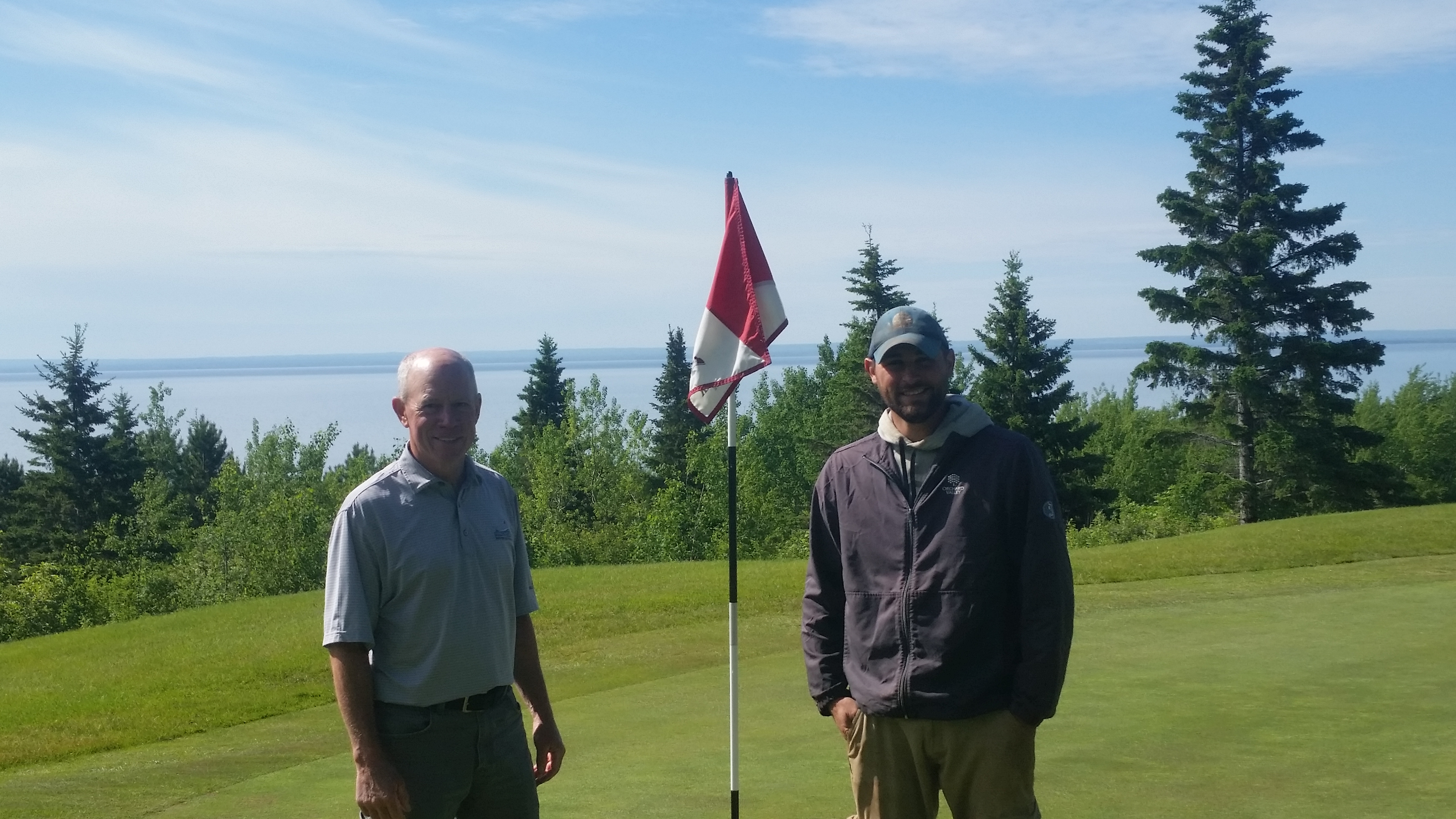 Dan and Dale at Lester Park Golf Course in Duluth, MN featuring green grass, a golf flag, pine trees and lake superior in the background.