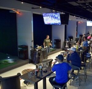 Golfers sitting at ZSTRICT with friends, watching tv and playing on the GOLFZON indoor simulators.