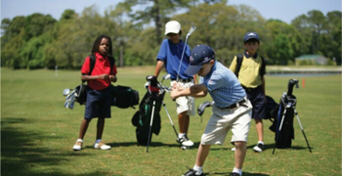Group of Young Golfers on a sunny day swinging on a tee box.